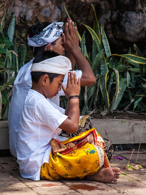 Samen bidden - Vader en zoon bidden in een tempel