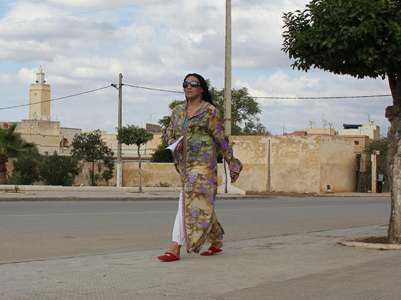 Onderweg - Deze dame in Ben Mellal (Marokko) is overduidelijk onderweg; misschien wel van traditie naar moderniteit!