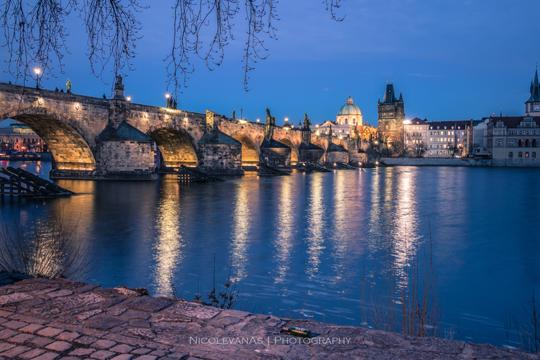 Charles Bridge by night. - Vanaf de kade met lange sluitertijd tijdens het blauwe uurtje de Charles Bridge in Praag gefotografeerd.<br />