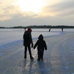 Grote zus leert klein broertje schaatsen