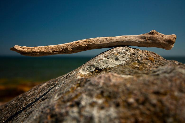 balance - Een verweerde tak ligt in balans op een rots aan de Rügense Oostzee-kust.