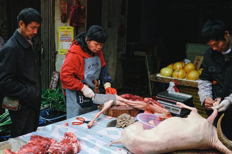 Slager in Guangzhou, China - Een slager aan het werk in een drukke markt in Guangzhou, China. De markt vormt een groot contrast met de moderne Shangxi