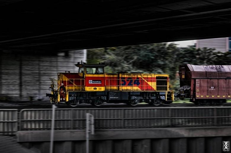 Bij Krupp Staalfabriek - Deze locomotief trekt 3 wagons waarvan de middelste geladen met vloeibaar staal; bij de Krupp Staalfabriek te Duisburg.