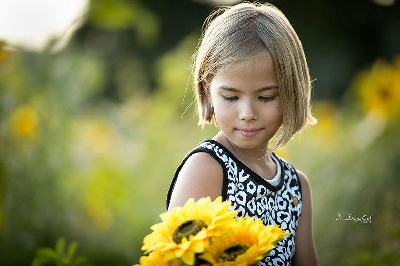 Girl with sunflowers - Alles kwam hier samen.. Mooi tegenlicht, een mooi model en het zonnebloemenveld als achtergrond. De zonnebloemen in haar hand h