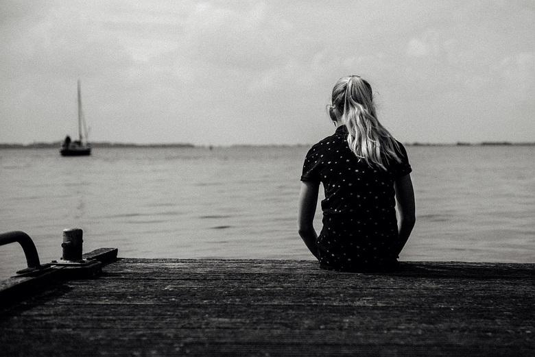 Sitting on the dock of the bay - Jonge tienerdame aan de waterkant op een steiger.