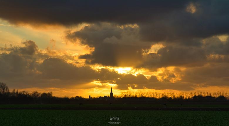 Zicht op Wognum - Mooie zonsondergang met zicht op de kerk van Wognum.