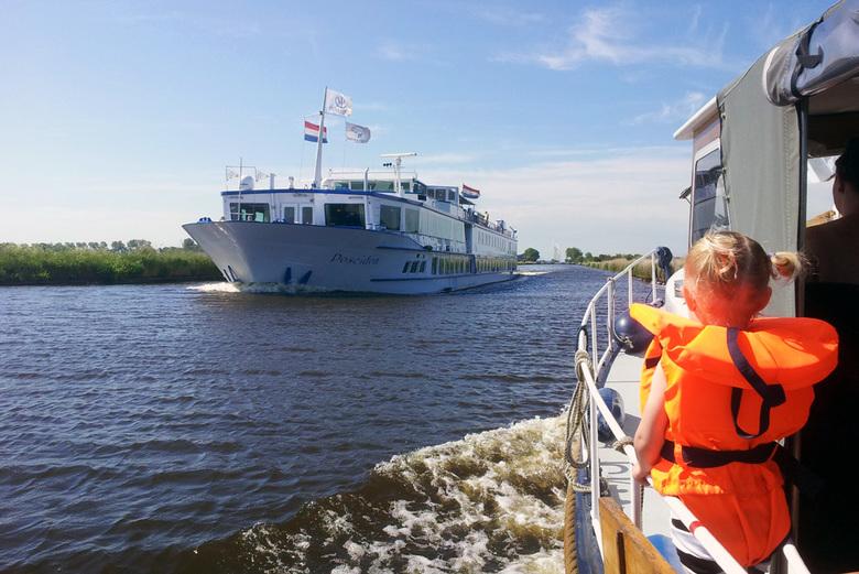 Vaarvakantie - Kleine boot ontmoet groot schip op Hollandse wateren.