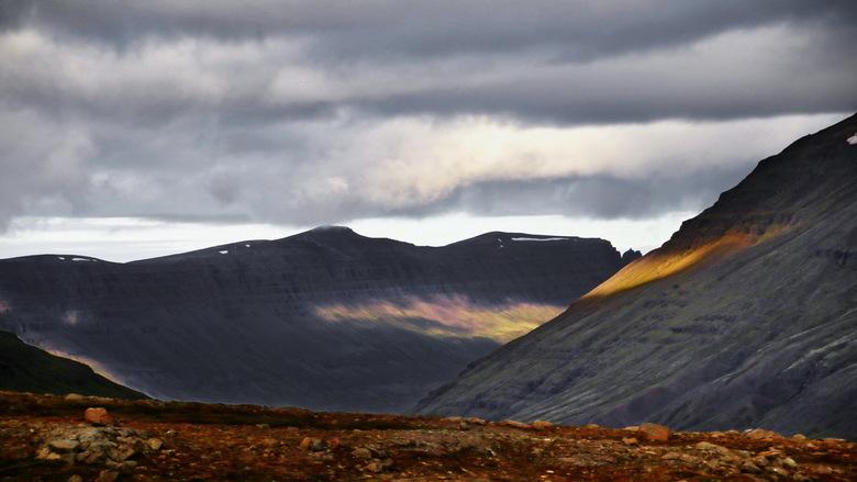 IJsland -12- - Het zonlicht maakt mooie heldere plekken op de bergwanden