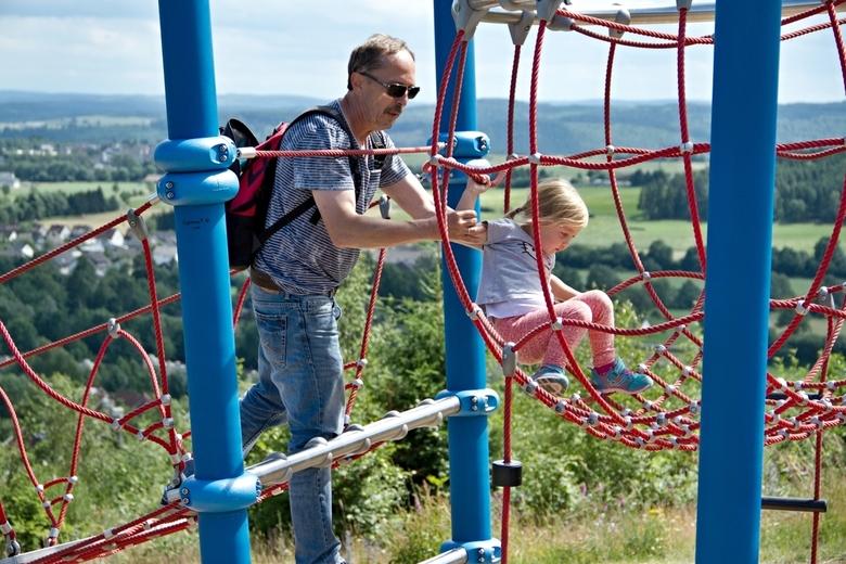 Vader en dochter bij een klimtoren.