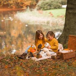 Spelende zusjes op kleedje in herfst bos