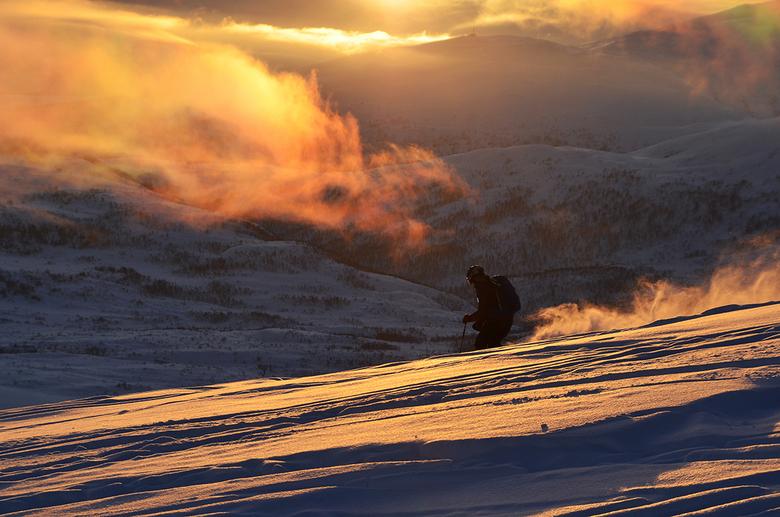 Sundown Skier II - Een skister daalt af van Rødtinden in de zonsondergang. <br /> <br /> Genomen op Rødtinden, nabij Tromsø, Noorwegen.