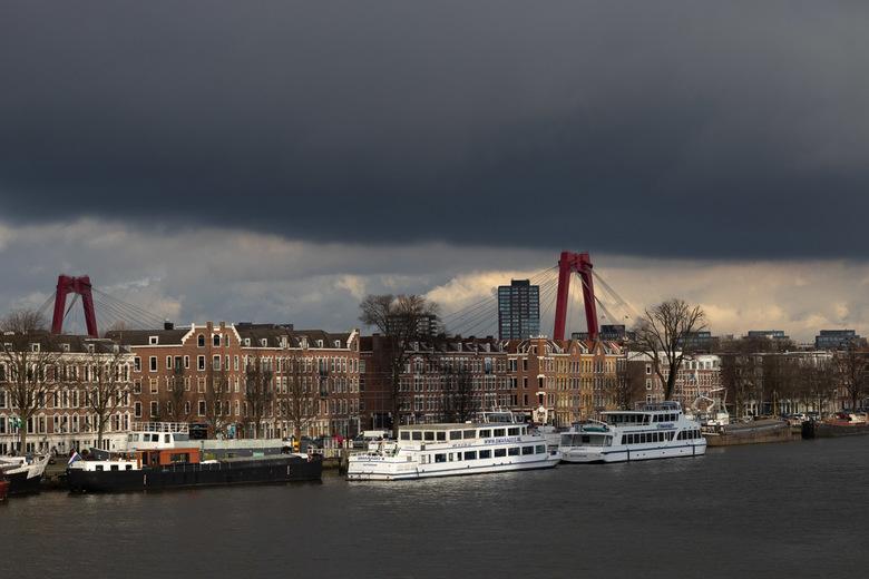 Donkere wolken pakken zich samen boven Rotterdam.  -