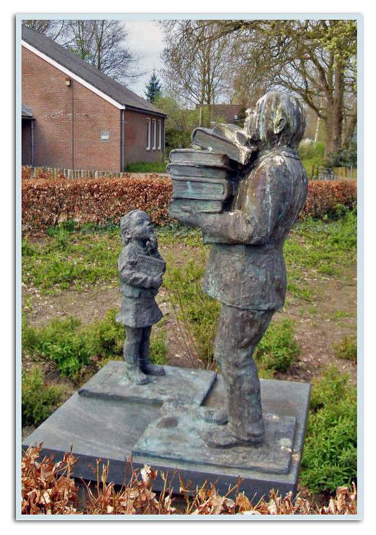 Man en meisje bij de bibliotheek. - Foto genomen in Zuiwolde (Dr.). De man neemt een stapel (studie)boeken mee naar huis, het meisje staat er verbaasd