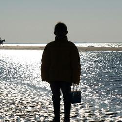 2 mensen genieten op hun eigen manier van zee en strand