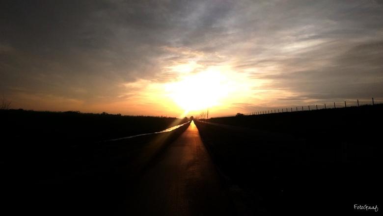 Endless road - Een mooie zonsondergang, gefotografeerd op mijn autorit in het Groningse landschap, eindeloze wegen zonder noemenswaardig verkeer tegen