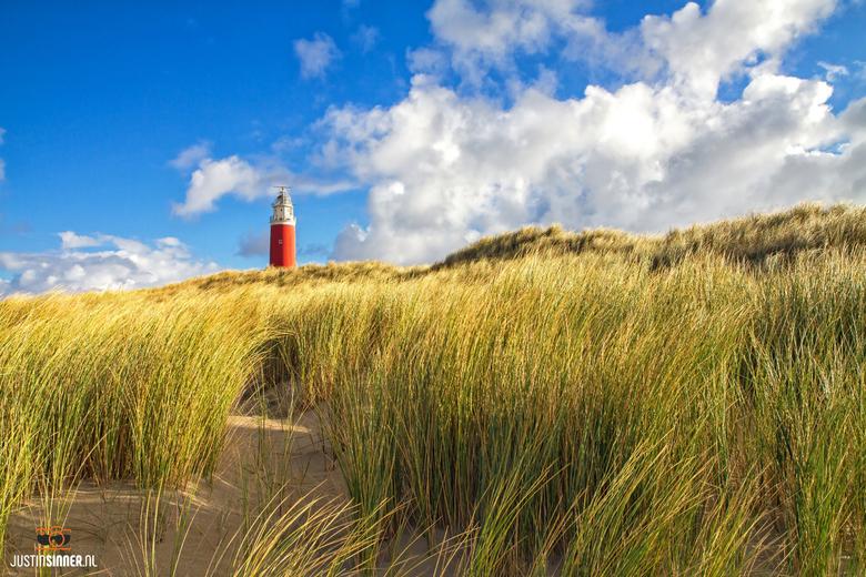 Texels Duinlandschap. - Texels plaatje, de prachtige duinen, blauwe lucht en rode vuurtoren. <br /> <br /> http://Justinsinner.nl/<br /> <br /> Fo