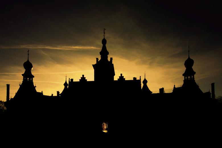 Ooidonk in silhouet - Kasteel van Ooidonk, maar nu in silhouet door tegenlicht. Je kunt mooi door de poort kijken naar de zon die de achterkant verlic