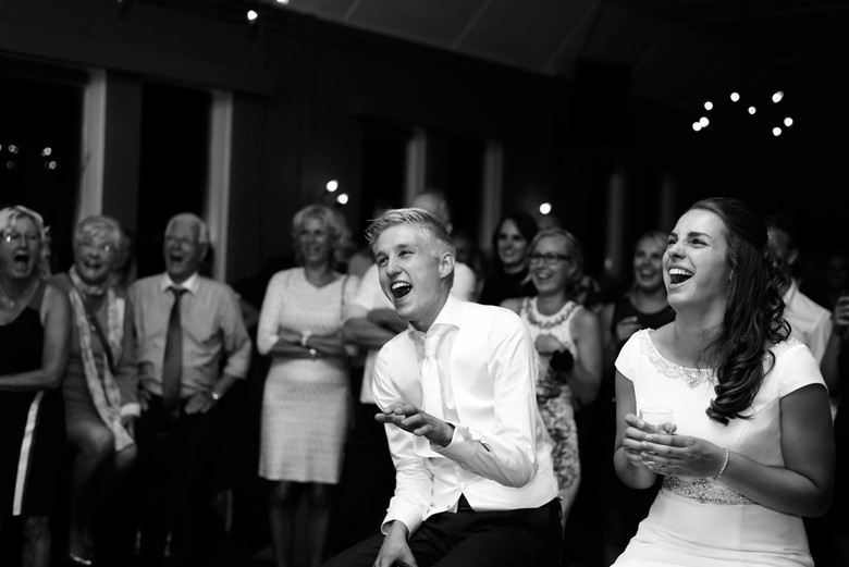 Blijdschap - Lachen tijdens een filmpje op een geslaagde bruiloft.