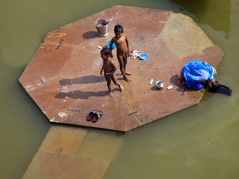 Haren wassen - Dit meisje zit op een plateau in de Ganges bij Varanasi en wast haar haar in de sterk vervuilde rivier.Of het daar schoner van wordt is