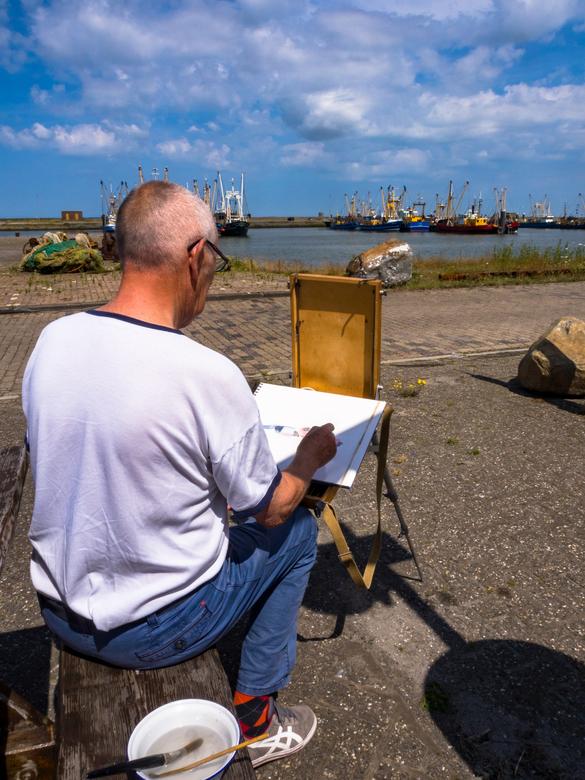 De schilder - De schilder aan het werk. <br /> In Lauwersoog was Joop Luining bezig met een aquarel van de boten in de haven.
