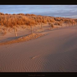 Geweven zand tijdens rode zonsondergang door asdeeltjes.