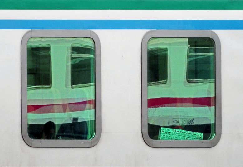 If you wish to be loved, love - Weerspiegeling van treinraampjes in treinraampjes. De treinen stonden stil op een italiaans station. Ook een krant met