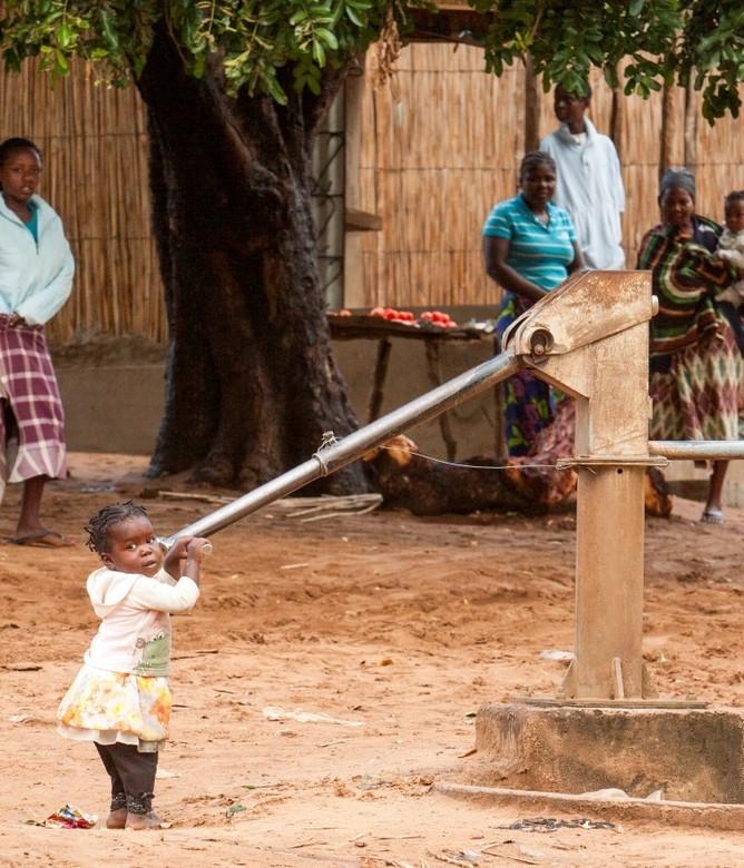 Kleine werkzaamheden - Een klein meisje speelt met een waterpomp die ze met moeite hoger krijgt dan dat ie omlaag gaat in een buitenwijk van Xai-Xai,