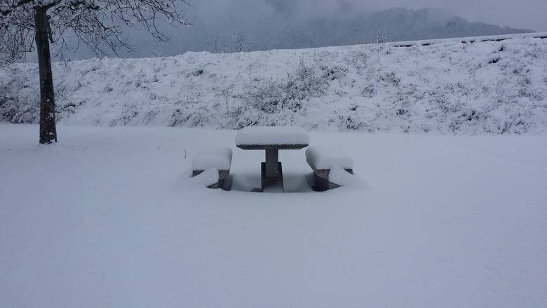 Picknicken? - Picknickbankje ondergesneeuwd in de bergen