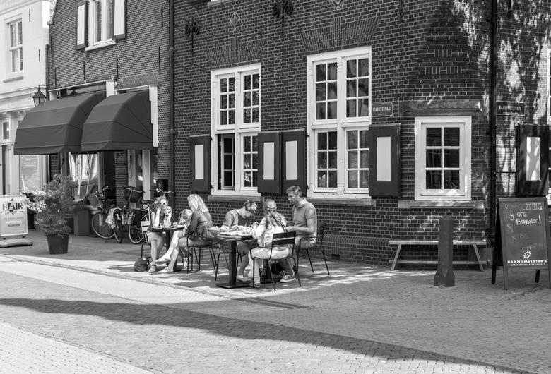 straatfotografie NAARDEN - mensen genieten van een rustplek op een een terras in Naarden