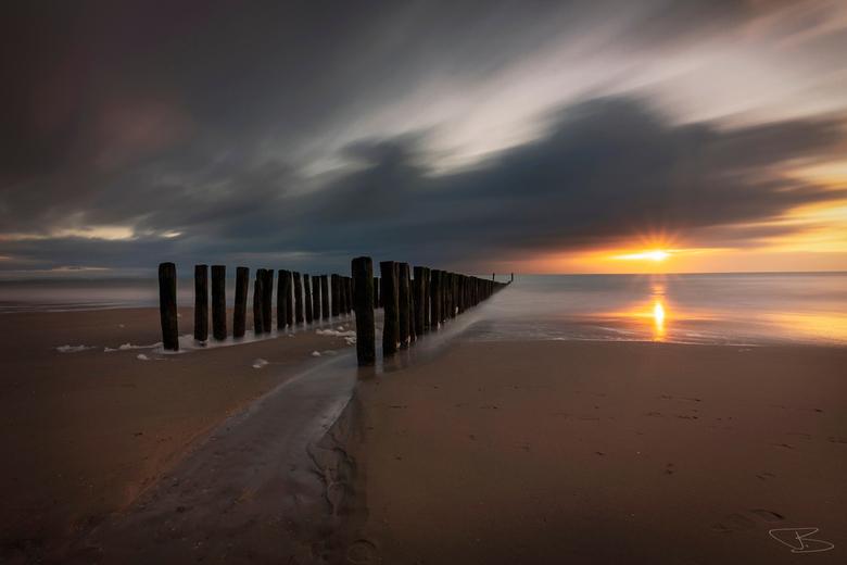 In the Shattering of Things - Een stormachtige zonsondergang aan het strand van Zoutelande, waarbij de zon nog een laatste keer doorkomt.