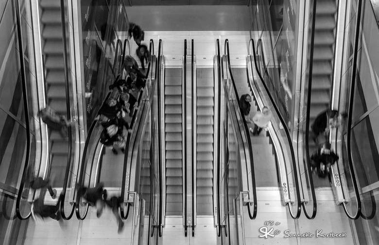 Lijnenspel in zwartwit - Lijnenspel... Roltrappen van boven gefotografeerd met een langere sluitertijd, maar niet te lang, anders zag je de treden nie