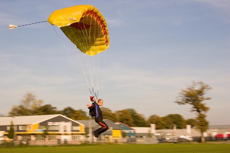 """Landing - Parachutespringer maakt """"swoop""""-landing op vliegveld Hoogeveen. Fototoestel meegetrokken, sluitertijd 1/125, RAW naar JPG en bewer"""