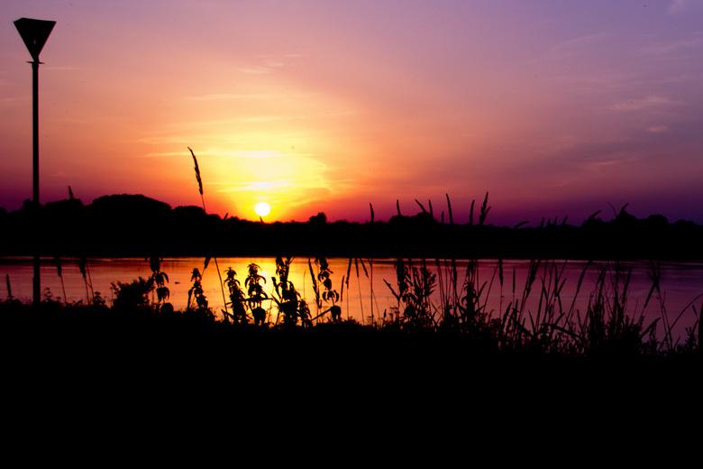 See you tomorrow - Zonsondergang aan de IJssel met een prachtig gekleurde lucht.