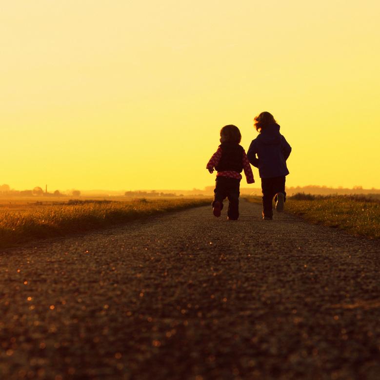 Golden future - Jongetje en meisje rennen samen op een pad, en de avondzon gaat bijna onder