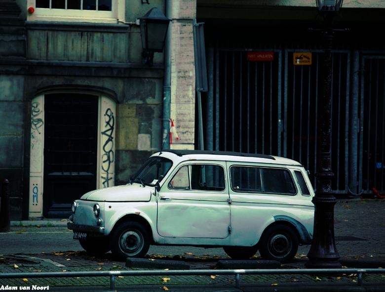 Fiat - Een niet in een perfecte staat oude fiat 600 aan de gracht in Amsterdam