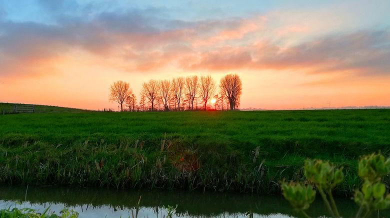 Leven en licht - Fietsend tussen de weilanden, en dan gaat de zon langzaam onder...