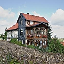 Huis met twee houten balkons boven elkaar.
