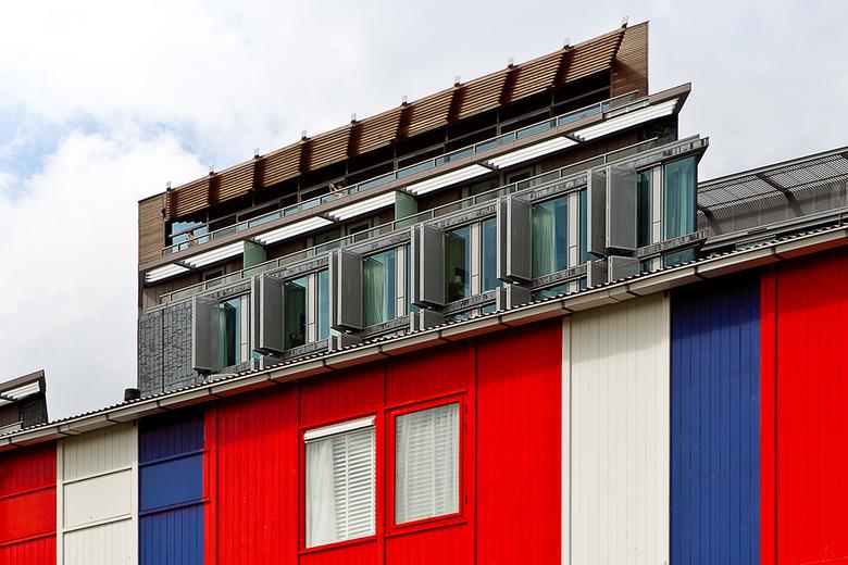 Optische Illusie - De kleurrijke werkketen en het nieuwe Mint-Hotel in Amsterdam smelten vanuit deze kijkhoek samen tot een merkwaardig architectonisc