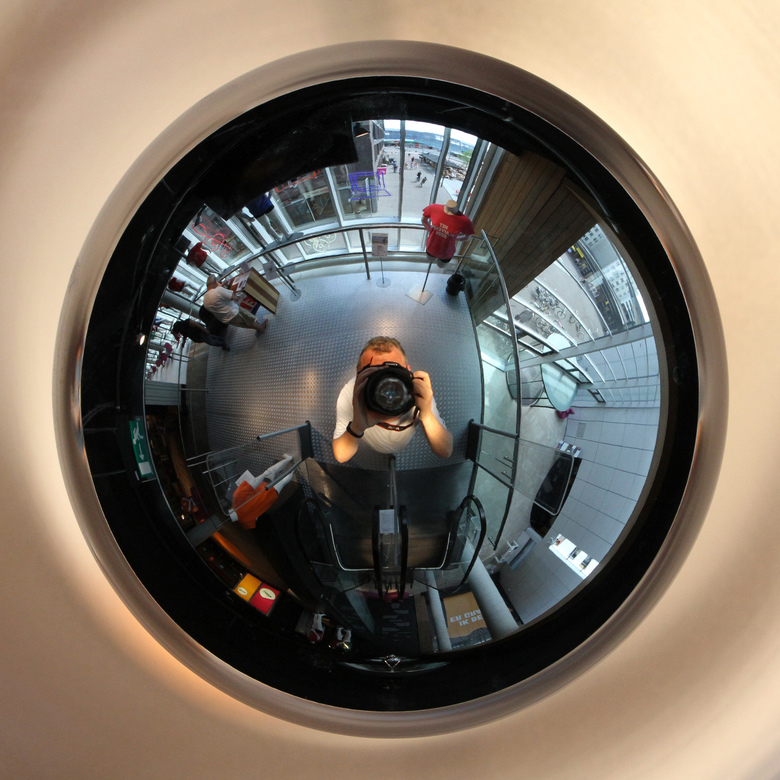 Zelfportret - In de gloednieuwe en fraaie bibliotheek in Lelystad hangen grote schalen met spiegelreflexlampen aan het plafond. Ze laten als een fish-