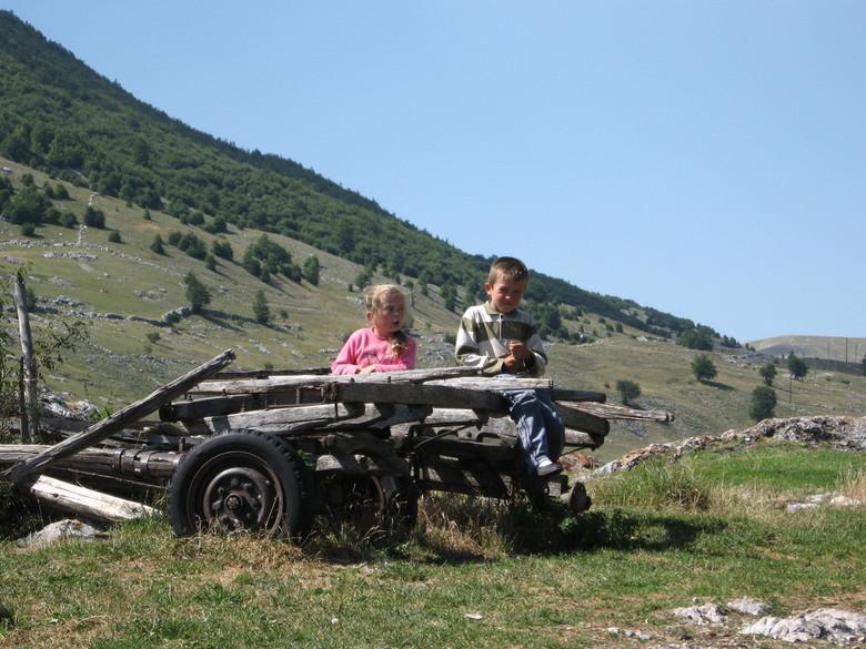 on a left behind peace of artillery - Kinderen gefotografeerd op een stuk artillerie in een authentiek dorp in Bosnië
