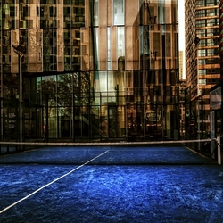 the city plays doubles on a dirty blue gravel playgrond