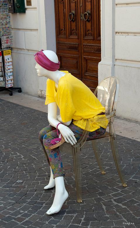 Modebeeld - Tijdens onze vakantie liepen we door een plaatsje aan het Gardameer en zag ik al pratende een vrouw op een stoeltje op straat zitten, je w