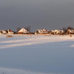 Zevenhuizen in zon met sneeuw en donkere lucht