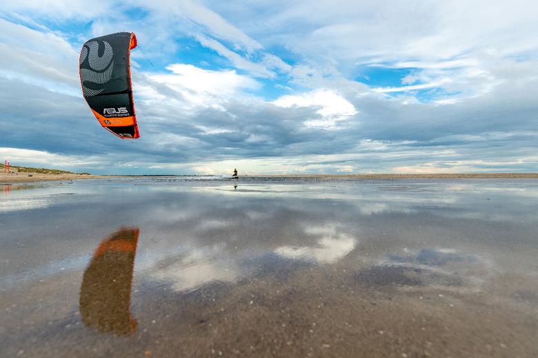 Kitesurfer met spiegeling van de lucht -