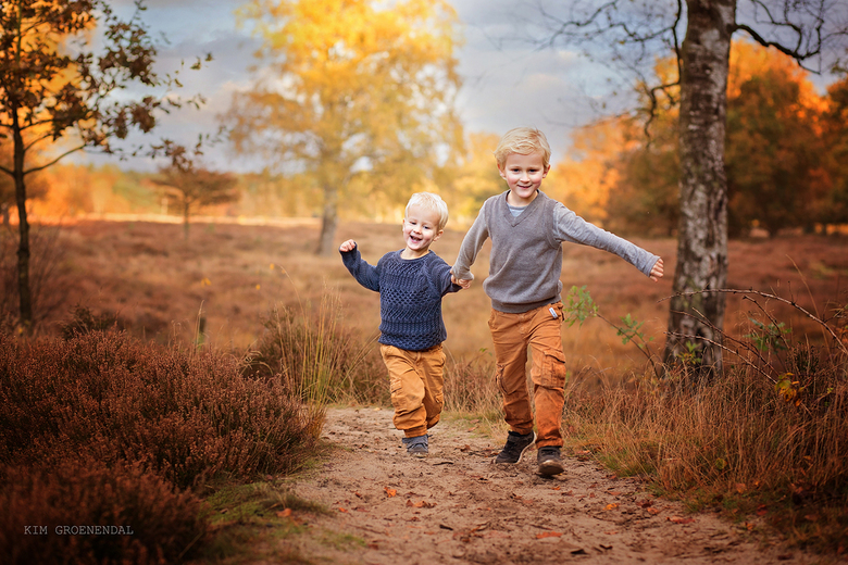 samen rennen in de herfst - Broertjes rennen samen over de heide