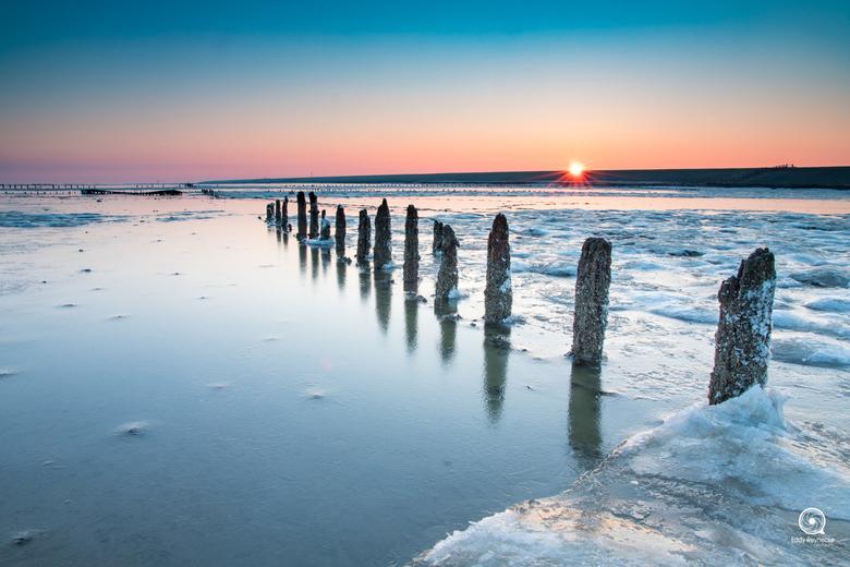 """Zonsopkomst Wierum - Zonsopkomst tijdens een koude ochtend aan de waddenzee bij Wierum met op de achtergrond het wrak <img  src=""""/images/smileys/wilt."""