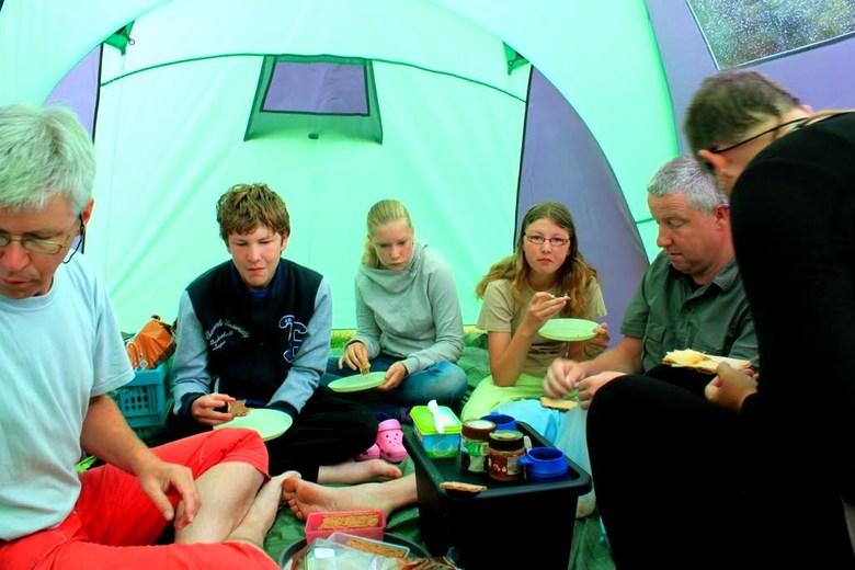 Met 7 pers gezellig onbijten in de tent  - Tijdens een kano vakantie in Noorwegen met familie eten gezellig we ons onbijt in de tent vanwege de regen.
