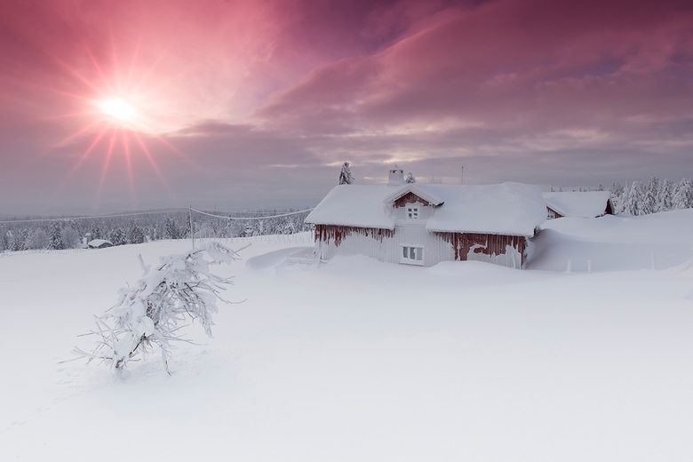 Zonsopkomst in ondergesneeuwd Noors dorpje