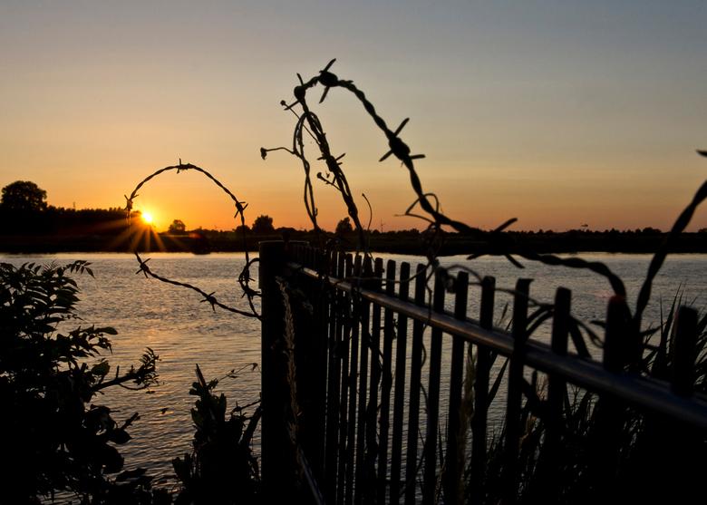 Doorkijkje - Ondergaande zon in een ring van prikkeldraad.
