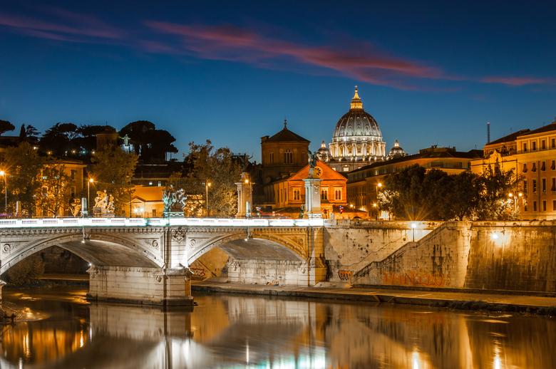 Blue hour in Rome, Italy - Foto van een brug over de Po, waarbij op de achtergron de Sint Pieter in Vaticaanstad zichtbaar is.